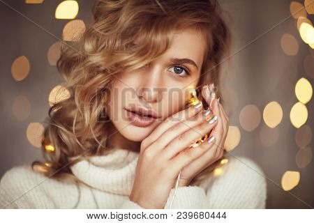 Beautiful Young Blond Girl In Sweater Holding Golden Garland And Looking Sensually At Camera.