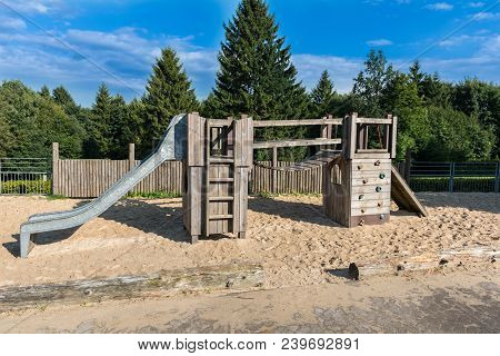 Children's Playground With Climbing Frame On The Edge Of The Forest In Front Of A Blue Sky