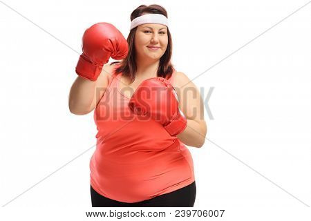 Overweight woman wearing a pair of red boxing gloves isolated on white background