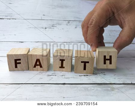 Hand building Faith word on wooden cubes