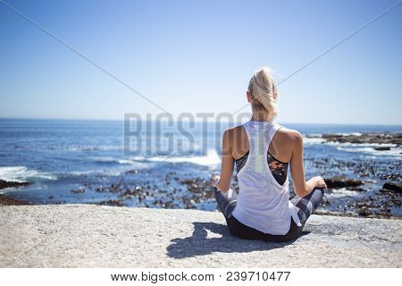 Blond Female Fitness Model Meditating And Doing Yoga On A Granite Rock Overlooking The Ocean