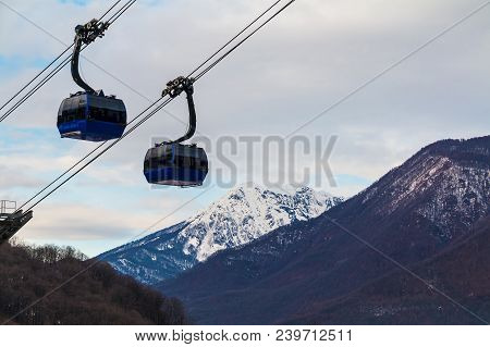 Two Cabins Of The Cableway In Krasnaya Polyana On The Background Of Snowy Mountains, Sochi, Russia