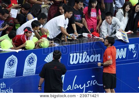 BUKIT JALIL, MALAYSIA- OCT 01: Serbia's Janko Tipsarevic (red) signs autograph after his Malaysian Open semifinal win over Japan's Kei Nishikori on Oct 01, 2011 in Putra Stadium, Bukit Jalil, Malaysia.