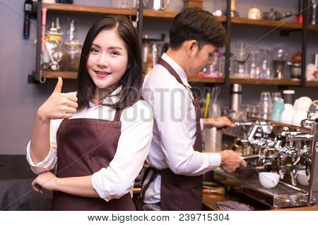 Asian Women Barista Smiling And Looking To Camera In Coffee Shop Counter.  Barista Female Working At