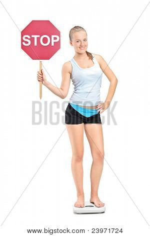 Full length portrait of a weightloss girl standing on a weight scale and holding a traffic sign stop isolated on white background
