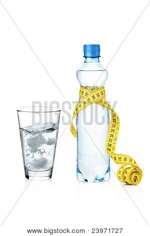 A yellow measure tape wrapped around a bottle and glass of water isolated on white background