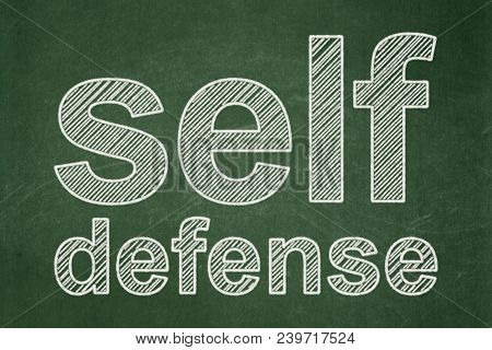 Protection Concept: Text Self Defense On Green Chalkboard Background