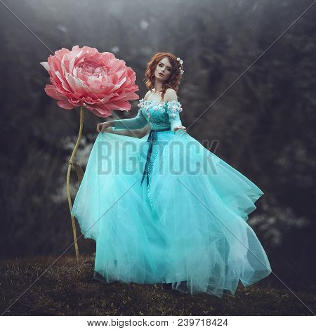A Beautiful Sensual Girl With Red Hair In A Fairy-tale Blue Dress Posing In The Wind Near A Huge Flo
