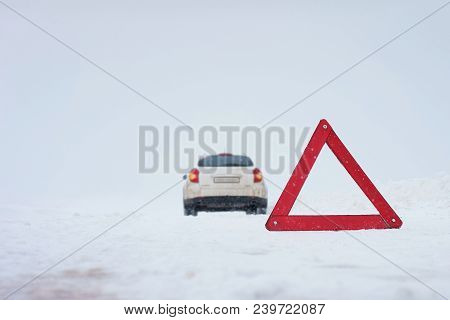 Winter Road, Snowstorm, Heavy Snow. Forced Stop. Warning Red Triangle. A Broken Car. Road Accident.