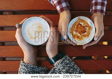 Female Hands Holding Cups Of Coffee On Wooden Table Background. Big Mugs Of Hot Latte Drink Warming