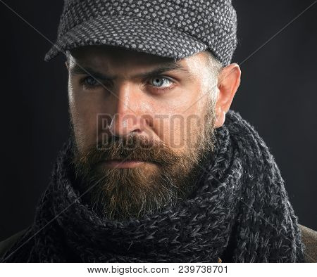 Fashion Man. Handsome Serious Male Model In Leather Jacket, Gray Cap And Scarf. Handsome Bearded Man