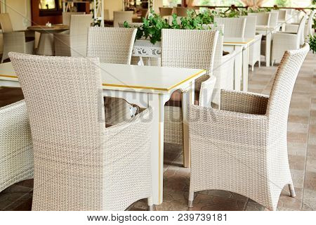 Empty Cafe With Rattan Wicker Armchairs And Tables On Summer Garden Terrace Outdoor, Free Space. Tab