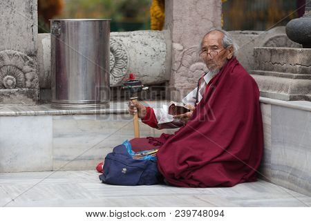 The Old Man - The Buddhist Pilgrim, Sits Under Walls Of Mahabodhi Temple, Reads Mantras And Rotates