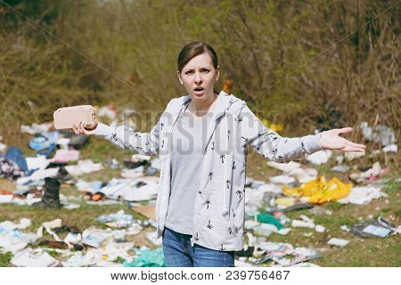 Young Upset Irritated Woman In Casual Clothes Cleaning Holding Rubbish And Spreading Hands In Litter
