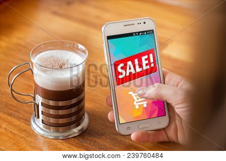 Girl With A Smartphone In Her Hands And A Sale Advertising On The Screen. Coffee Cup On The Table. M