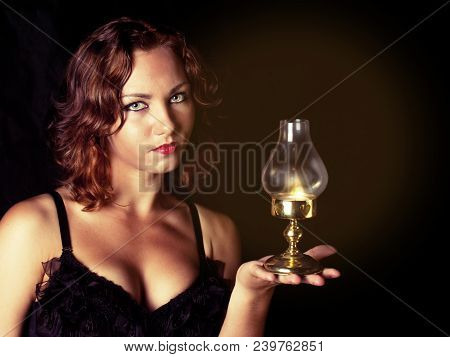 Young Girl In A Black Corset Holds A Retro Lantern In A Dark Room