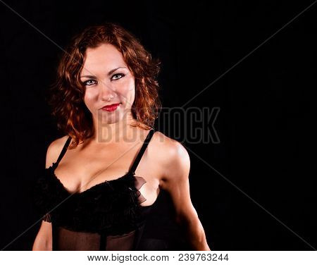 Portrait Of A Young Smiling Womanl In A Black Corset On Black Background