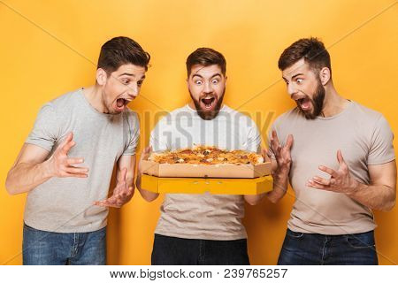 Three young excited men holding a big pizza isolated over yellow background
