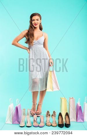 Full length photo of happy shopper woman 20s in dress posing with different summer shoes and holding shopping bags in hands isolated over blue background