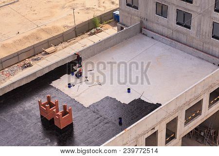 Two Workers Conduct Waterproofing Of The Roof With Bitumen. View From Above.