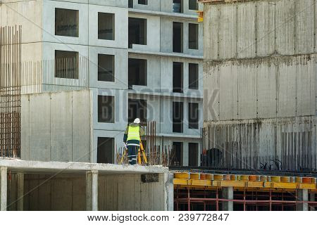 The Builder In Yellow Overalls Makes A Topographic Survey Against The Background Of A Concrete Wall,