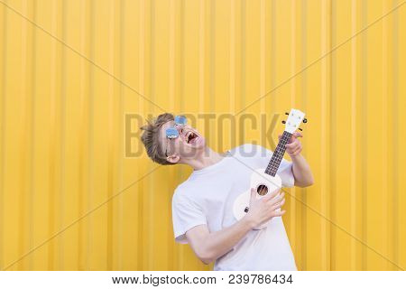 Crazy Young Man Plays Ukulele On A Yellow Background. Expressive Musician Playing Guitar. Musical Co