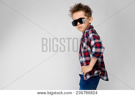 A Handsome Boy In A Plaid Shirt, Gray Shirt And Jeans Stands On A Gray Background. The Boy In Black