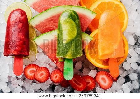 high angle view of some different homemade ice pops, made with different natural fruit juices and pieces of fruit, such as watermelon, strawberry, peach, lime or orange, placed on ice