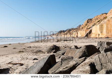 Solana Beach, California/usa - April 22, 2018:  People Play At The Shoreline On The Beach Near Cliff