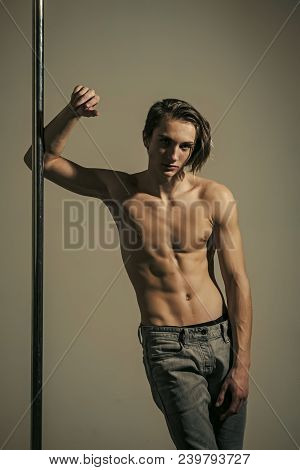 Shirtless Man Pole Dancing On A Grey Background. Young Strong Pole Dance Man With Nude Torso Stand N
