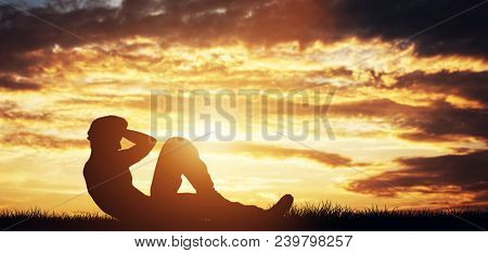 Man doing crunches outdoors in the sunset. Bodybuilding. Exercising and workout.