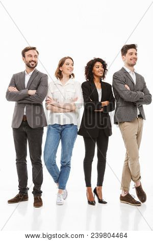 Full length portrait of a group of happy multiracial business people standing with arms folded and looking away isolated over white background