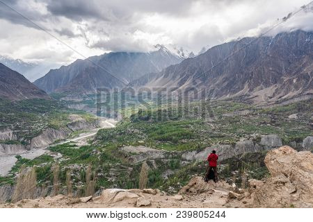 Photographer In Red Jacket Taking Landscape Photograph On Mountain Peak Cliff At Hunza Valley In Pak