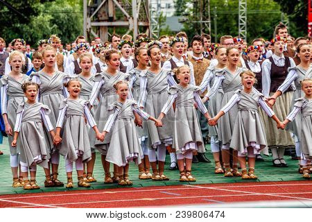 RIGA, LATVIA - JULY 11, 2015: Dancers perform at the Grand Folk dance concert of Latvian Youth Song and Dance Festival in the Daugava Stadium.