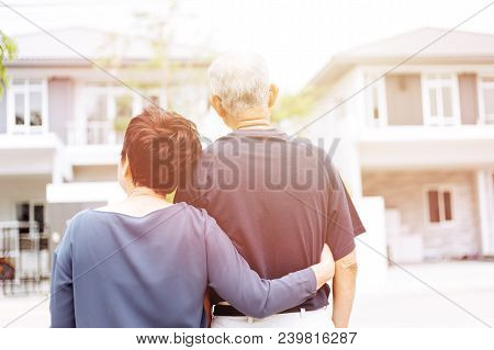 Happy Senior Couple From Behind Looking At Front Of House And Car. Warm Tone With Sunlight