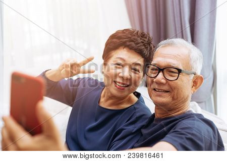 Senior Asian Couple Grandparents Taking A Selfie Photo Together At Home
