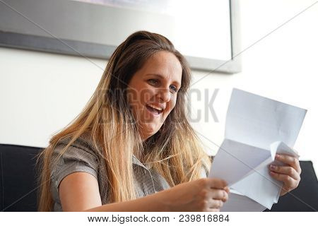 Happy Woman Enjoying Good News In Writing. The Girl Reads A Letter With Good News Sitting On The Cou