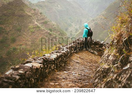 Hiker With Backpack On The Mountain Edge Cobbled Path Looking Down The Valley. Rocky Terrain Of High
