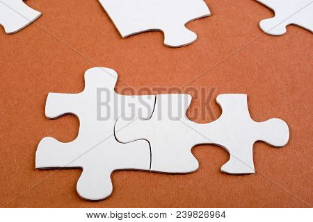 Two Pieces Of Jigsaw Joined. A Simple Cardboard Jigsaw On A Rough Paper Background. Concepts Of Solu