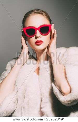 Gorgeous blonde woman posing in luxurious fur coat and pin-up sunglasses. Fashion, beauty. Studio shot.