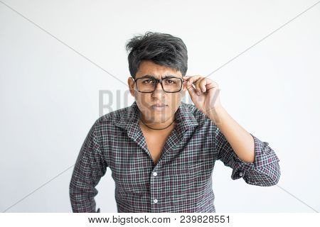 Surprised Young Indian Man Staring At Camera Through Glasses. Surprising News Concept. Isolated Fron