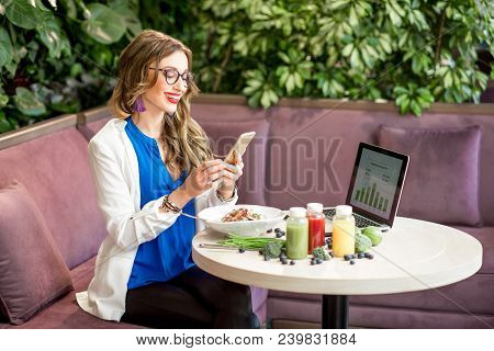 Young Business Woman Working During The Lunch With Healthy Food Sitting At The Vegetarian Restaurant