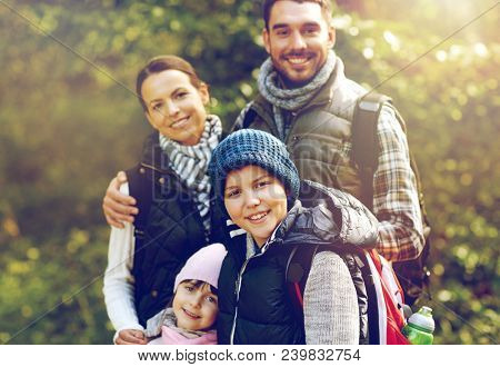 travel, tourism, hike and people concept - happy family walking with backpacks in woods