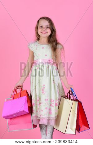 Girl With Happy Face Holds Shopping Bags On Pink Background. Schoolgirl With Red, Pink And Yellow Pa