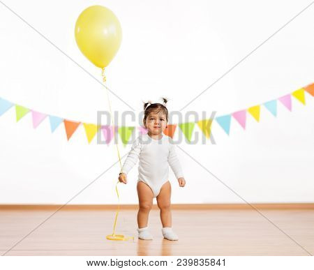 childhood, people and celebration concept - baby girl with helium balloons on birthday party