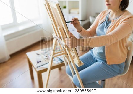 fine art, creativity and people concept - close up of artist with easel and paintbrush painting at studio