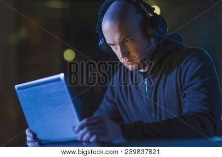 cybercrime, hacking and technology concept - male hacker with headset using laptop computer for cyber attack or wiretapping in dark room