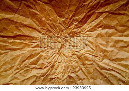 A Background Of Wrinkled Brown Wrapping Paper With Creases Radiating From The Center. Processed With
