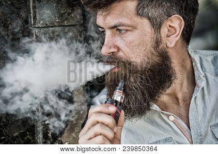 Bearded Man Smokes Vape, White Clouds Of Smoke. Electronic Cigarette Concept. Man With Long Beard Lo
