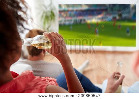 drinks, sport and leisure concept - happy woman friends drinking non-alcoholic beer and watching watching soccer or football on projector screen at home
